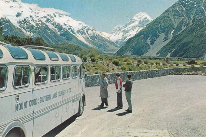 View of Mount Cook from a carpark. A bus can be seen to the left and three people on the right stand looking at the mountain