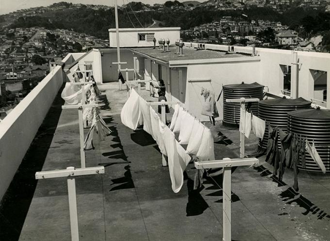 Black and white photo of a woman hanging out the washing on the roof of an apartment complex