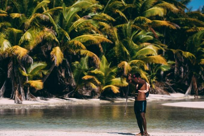 A man on a tropical island holds a rod