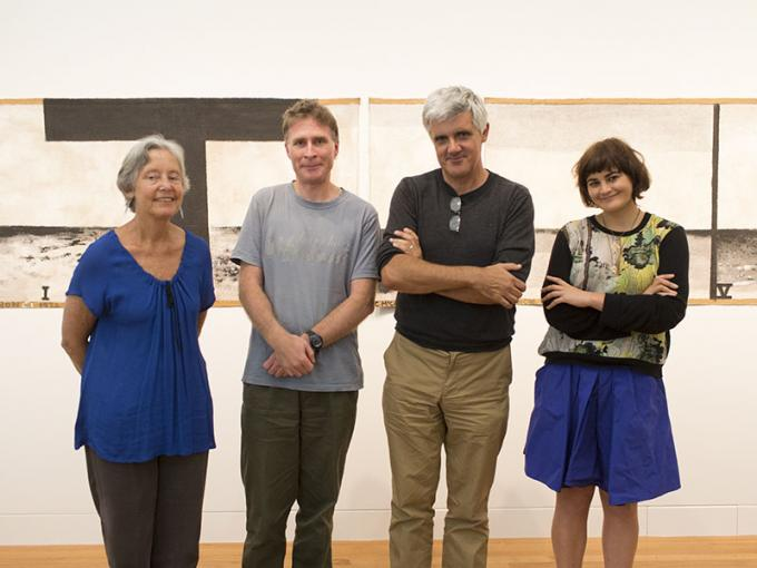Four people stand in front of Colin McCahon's 'Walk (Series C)'