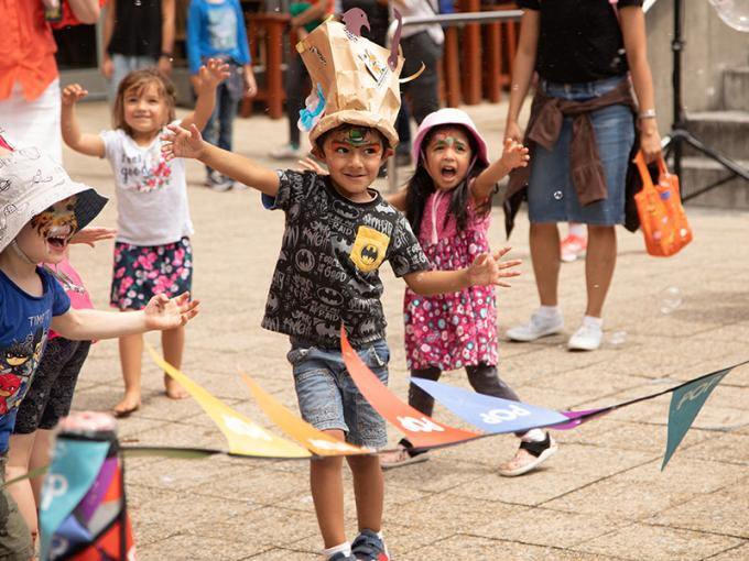 Children with facepaint on playing in front of flags