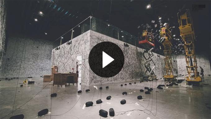 Still from a video. It shows a large pavilion in the middle of a room, three scissor lifts, and multiple strands of black wool hanging from the ceiling mid-installation