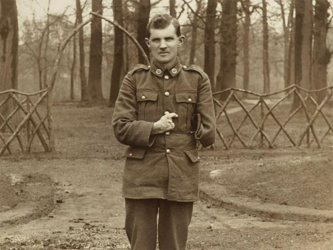 A soldier with one arm poses for a picture in a park