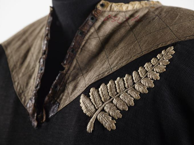 Close-up of 1905 All Blacks jersey, featuring a brown crest on the top and a large silver fern on the left-hand side. The jersey is black