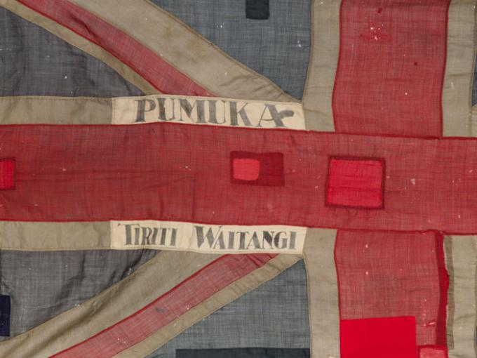 A Union Jack flag with the words Pumuka and Tiriti Waitangi embroidered on