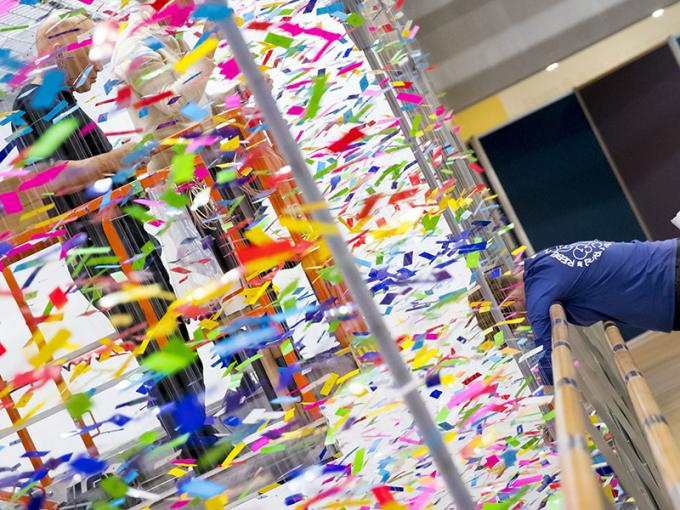 A person on a scissor lift is obscured by a dense collection of strands of colourful pieces of plastic hanging from the ceiling while another person looks over a bridge beside the work down towards the floor, where the work continues