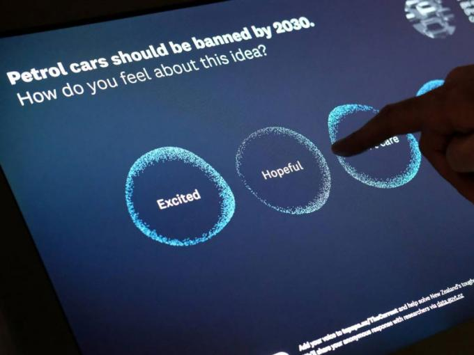 Visitor plays with a digital screen on it the words says 'Petrol cars should be banned by 2030. How do you feel about this idea?'