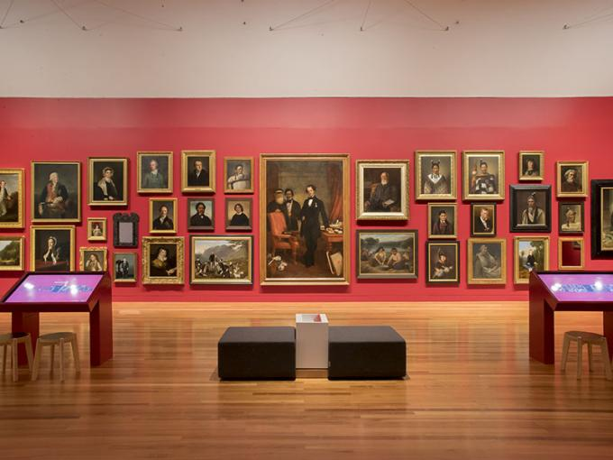 The wall of portraits in the gallery