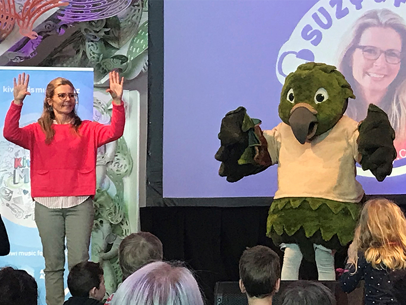 Suzy Cato shares a stage with Kahu the Kea, a person dressed in a large kea costume