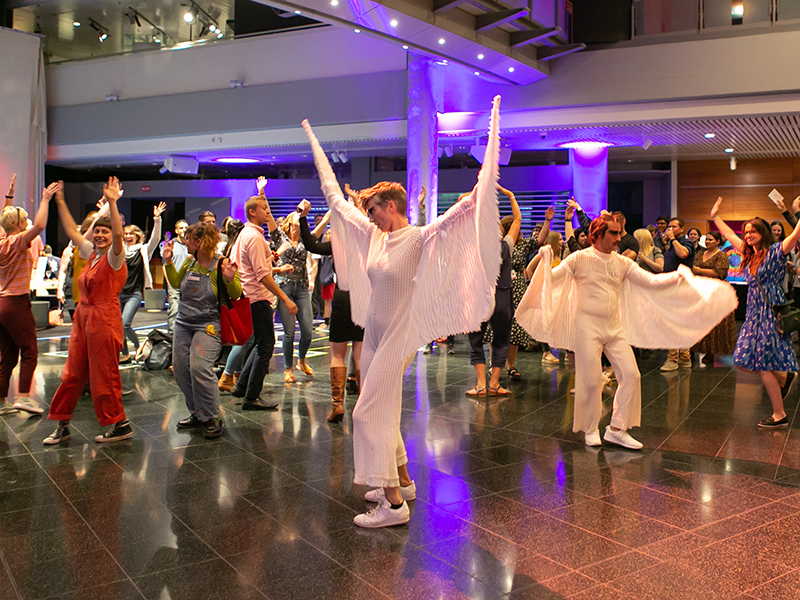 People dancing in a large space. Two people have white costumes that have wings on poles